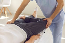 Hands of professional man osteopath in blue medical uniform fixing man patients knee and leg joints during visit at rehabilitation theapy in manual therapy clinic. Osteopath during work