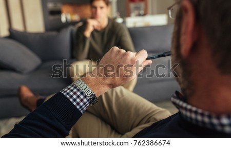 Hands of psychologist holding a pen and listening to man during therapy session. Psychotherapist understanding problems of a male patient. Foto stock ©