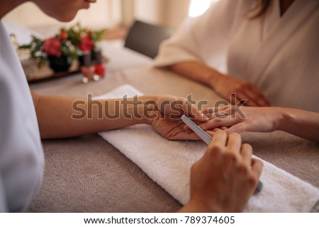 Hands of qualified manicurist filing the nails of woman client with a white buffer in nail salon. Focus on hands of manicurist shaping nails of female client in salon. Stok fotoğraf ©