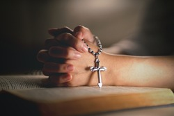 hands of religious christian woman holding jusus cross rosary praying to god with holy bibble book in chruch