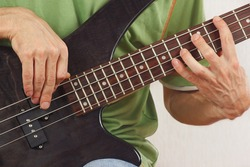 Hands of rock musician playing the electric bass guitar