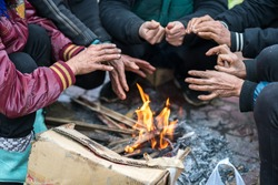 Hands of rural minority people warming up around the fire during the cold weather days in mountaious region in Vietnam