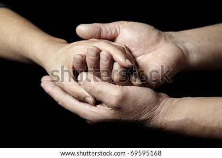 Hands of senior people supporting each other on a black background