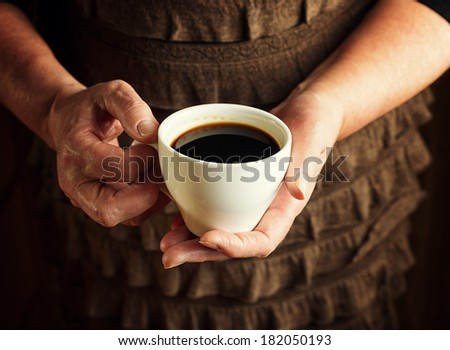 Hands of senior woman holding cup of coffee.
