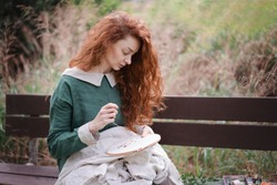Hands of slim young woman with ginger curly long hair embroider on embroidery frame sit on bench in spring summer garden among green grass in stylish linen dress. fancywork classes, stitching school