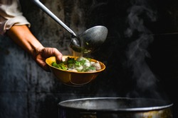 Hands of Thai Chef are scooping a delicious soup topped with noodles and pork balls in the corner of the restaurant with light shining to the noodle bowl that is traditional Thai food.