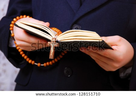 Hands of the boy going to the First Holy Communion holding prayer book and a rosary