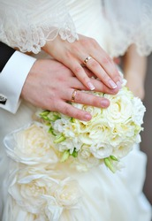 hands of the bride and groom with rings on wedding bouquet.