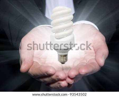 Hands of the businessman hold a luminescent lamp