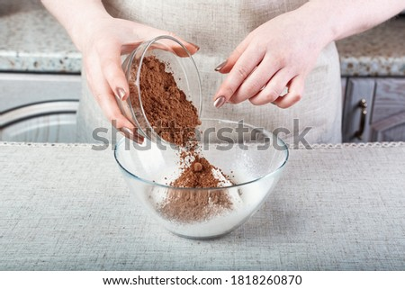 hands of the chef pour cocoa powder into a glass container with flour Foto stock ©