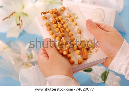 hands of the girl going to the First Holy Communion keeping a  prayer book and a  rosary
