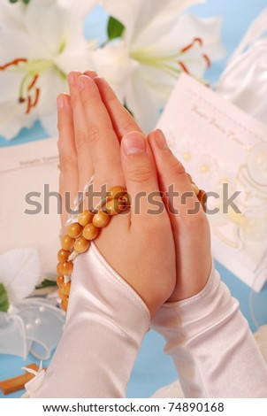 hands of the girl going to the First Holy Communion set in amen and  praying with a  rosary