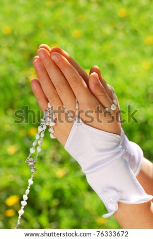hands of the girl going to the First Holy Communion set in amen and praying with rosary against green grass background
