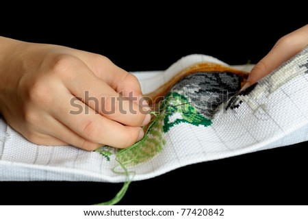 Hands of the girl working upon the embroidery, located on a black background.