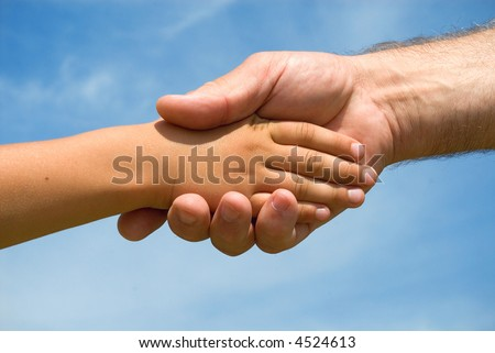 Hands of the grandfather and grandson on a background of blue sky