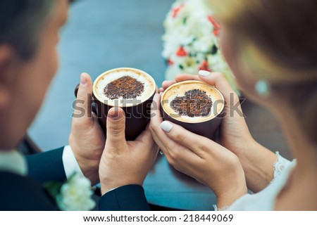 Hands of the groom and the bride and coffee cups on the table #218449069