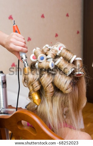 Hands of the hairdresser doing celebratory stacking of hair to the bride