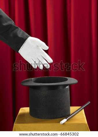 Hands of the magician with top hat and magic wand on stage.