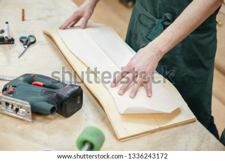 Hands of the master carpenter pressed against the board mold to cut a skateboard from a wooden board. Concept of creating exclusive wooden products on order #1336243172
