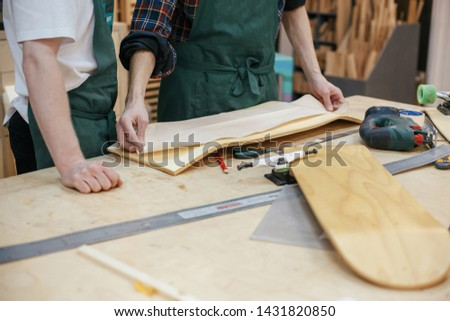 Hands of the master carpenter pressed against the board mold to cut a skateboard from a wooden board. Concept of creating exclusive wooden products on order #1431820850
