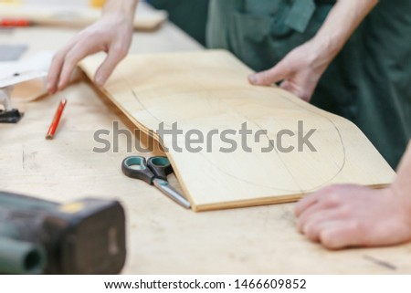 Hands of the master carpenter pressed against the board mold to cut a skateboard from a wooden board. Concept of creating exclusive wooden products on order #1466609852