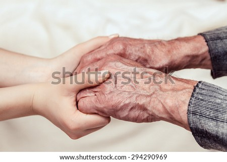 Hands of the old man and a young woman. toning