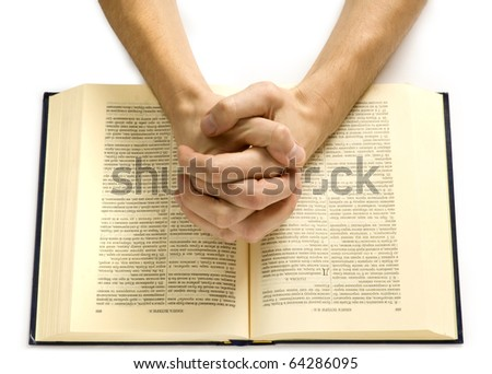 Hands of the praying man lie on the bible