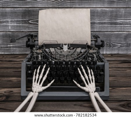 Hands of the skeleton prints on a vintage typewriter. Empty sheet of old paper for your ad design text