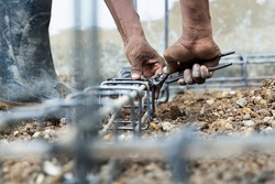 Hands of the workers are binding the wire with steel bars at the construction site, knitting metal rods with steel bars for concrete