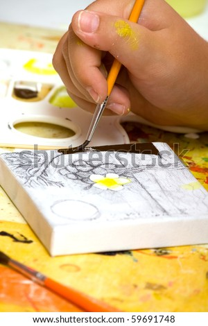 Hands of the young artist of the miniature painter drawing a picture.Work of the artist.