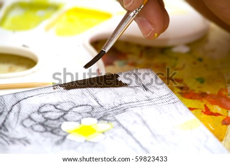 Hands of the young artist of the miniature painter drawing a picture.Work of the artist. - stock photo