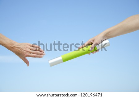 Hands of track and field athletes with relay baton, symbol for teamwork, partnership, cooperation, isolated with blue sky as background and copy space. - stock photo