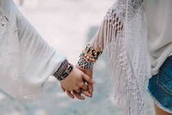 Hands of two young girls wearing hippy clothes with bracelets.  Contemporary bohemian style. Spirit of freedom. Fashion shot.
