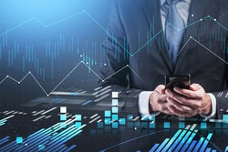 Hands of unrecognizable businessman using smartphone over blurry blue background with double exposure of graphs. Toned image