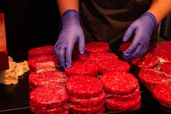 Hands of unrecognizable butcher handling raw burgers for sale, gastronomy concept