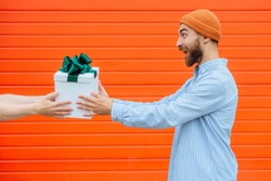 hands of unrecognizable man giving gift box with green bow for surprised caucasian hipster beard man in orange hat with on red background. Black Friday shopping, gifts, holiday concept. Side view