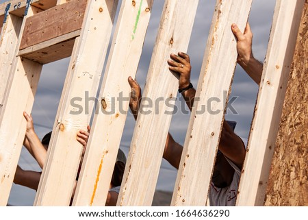 Hands of volunteers raising a wall for a Habitat for Humanity home