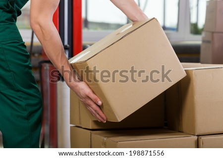 Hands of warehouse worker lifting box, horizontal