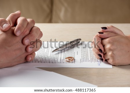 Hands of wife and husband signing divorce (dissolution, canceling marriage, legal separation) documents, filing divorce papers or premarital agreement prepared by lawyer. Wedding ring in the center  #488117365