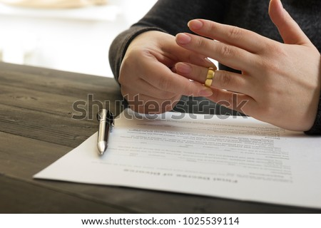 Hands of wife, husband signing decree of divorce, dissolution, canceling marriage, legal separation documents, filing divorce papers or premarital agreement prepared by lawyer. Wedding ring #1025539114