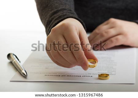 Hands of wife, husband signing decree of divorce, dissolution, canceling marriage, legal separation documents, filing divorce papers or premarital agreement prepared by lawyer. Wedding ring #1315967486