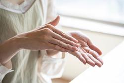 Hands of woman applying hand cream