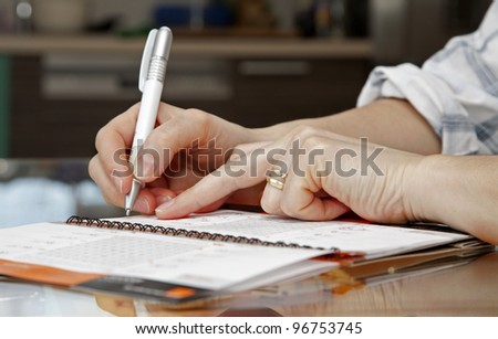 hands of woman by writing in a calendar