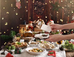 hands of woman holding Christmas Eve wafer at the festive table with traditional dishes