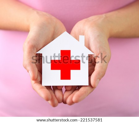 Hands of woman holding paper house with red cross