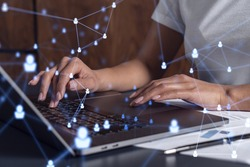 Hands of woman hr specialist is typing the keyboard in the internet to find the best candidates to create international network in recruitment process. Casual wear. Social media hologram icons.