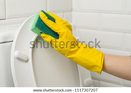 Hands of woman in yellow protective rubber gloves wash the toilet. #1117307207