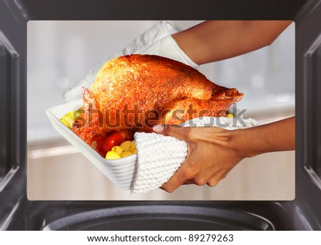 hands of woman is taking out  turkey with potato from oven