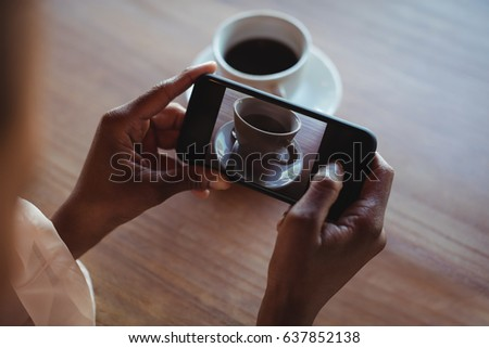 Hands of woman taking a clicking picture of black coffee in restaurant