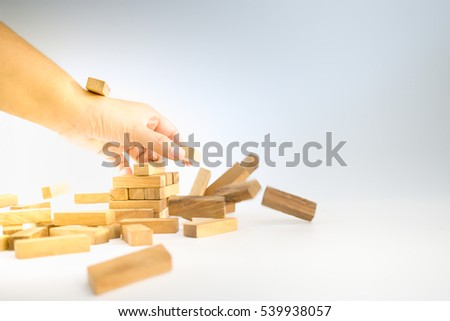 Hands of woman took  the brick and destroyed the wooden block tower. #539938057